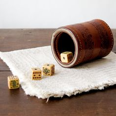 """hand-tooled and felt-lined leather cup with five carved dice. bottom appears to be dated 1938 in handwriting. 3.75"""" tall x 3"""" diameter. dice measure .75"""" each side. all vintage sales are final."""