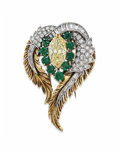 A COLORED DIAMOND, DIAMOND AND EMERALD BROOCH - Set with a marquise-cut fancy intense yellow diamond, weighing approximately 3.21 carats, within a circular-cut emerald surround, to the circular and baguette-cut diamond scrolling plaque, mounted in platinum and 18k gold.