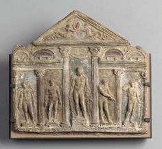 Relief showing a scene in a palaistra wrestling school, 1st century A.D. This relief shows reliefs placed between the columns of a corinthian gabled facade, winged tritons are shown in the gables and in the intercolumnar spaces are reliefs, from left to right showing boxers with cestus, statue of Herakles, an athlete cleaning his strigil and a victor with a palm, 45 cm high. Louvre museum