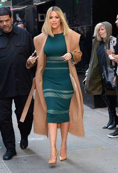 Khloe Kardashian beige trench coat with deep green dress sheer cutouts