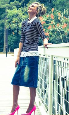 Mid-length stretch denim skirt with button fly closure.