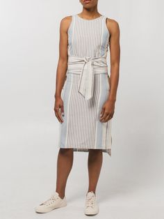 Our favorite sleeveless shift dress with a flattering waist wrap that falls just below the knee. Featured in our custom textile exclusively woven in a multi stripe fabric, a lightweight dress perfect for day or night in natural blue and nude shades. Available in size XS, S, M or L.100% cotton Handmade in Guatemala Machine wash cold on delicate cycle, lay flat to dry.Due to the handmade weaving nature of our clothing each piece varies slightly in texture and color. We love that one-of-a-kind…