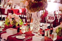 """centerpiece -- baseballs in glass vases with flowers at top (notice the """"baseball"""" table numbers and Coke glasses with straws!)"""