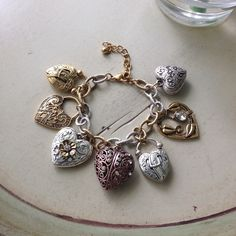 Silver, gold and rose gold charm bracelet Adorable mixed metals charm bracelet. 7 hearts with different designs. Lobster clasp closure. Feel free to ask me any questions😊 *this is a costume jewelry piece. Jewelry Bracelets