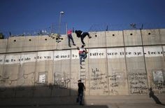 Palestinians, not permitted by Israeli security forces to cross into Jerusalem from the West Bank due to an age limit, climb over a section of the controversial Israeli barrier as they try to make their way to attend the first Friday prayer of Ramadan in Jerusalem's al-Aqsa mosque, in the village of Al-Ram, near Ramallah June 19.