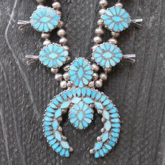 Frank Dishta, Zuni,  is considered to have pioneered the flush turquoise settings characteristic of the family's work. This necklace dates to the 1930's. It's a classic sterling or coin silver necklace, with diamond shaped turquoise stones in the centers of the flowers and on the crescent Naja. The turquoise has lovely variegation, appropriate for its age. Squash Blossom Necklace - The Curator's Eye