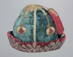 Man's cap, 18th century. Grey blue velvet with stamped floral pattern; brim, red velvet. In each section of crown roughly trefoil shaped ornaments of appliqué red velvet and silk and metal brocade, pendant from appliqué narrow gold ribbon.