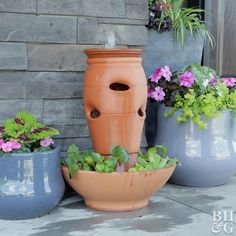 Constructed with a strawberry jar azalea pot and terra-cotta bowl this fountain is ideal for a deck or patio. It will beckon you to relax by its soothing bubbling water. Constructed with a sterra-cotta fountain front porch among potted plantsLandscape Ide Garden Yard Ideas, Garden Crafts, Garden Projects, Garden Ideas Videos, Diy Water Fountain, Garden Water Fountains, Fountain Garden, Homemade Water Fountains, Fountain Ideas