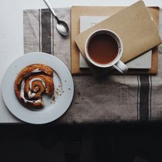 Cup of tea on a pile of notebooks with a pastry