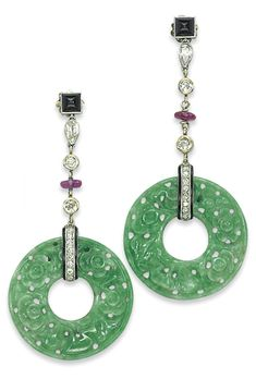 A PAIR OF ART DECO JADEITE, ONYX, RUBY AND DIAMOND EAR PENDANTS, BY CARTIER, CIRCA 1922. Each designed as a pyramidal cabochon onyx top suspending a chain of diamond collets and ruby bead, with carved and pierced jadeite disc pendants, mounted in platinum, 5.8 cm. Signed Cartier. #Cartier #ArtDeco #earrings