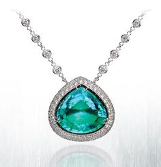 This 18.32 carat pear shaped paraiba is as breathtakingly beautiful as it is rare. Set in platinum, the mesmerizing emerald green and blue color is only further complemented by 9.60 carats of pave and bezel set round brilliant diamonds. By Lugano Diamonds.