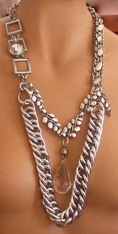 Statement Jewelry designed to be a bold, chunky chain piece. Lots of silver tone chains and a large faceted drop. The necklace adjusts to several lengths and looks great with a simple tee and jeans or a little black dress. Measures 26 inches.