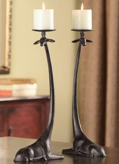 Sitting Giraffe Pillar Candle Holders -Intriguing set of two modern design Giraffe candle holders with elongated necks supporting round candle holder plates on top of their heads. The cast aluminum Giraffes are in a sitting position with foreshortened front legs and their tall necks curve gracefully upward. Polished with a lustrous bronze patina. Candles Not Included.