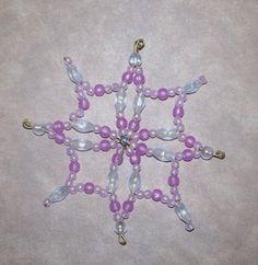 """Dieser Perlenstern wurde mit rosa und weißen Wachsperlen gestaltet. Als Gerüst dient ein einfacher Drahtstern. Zusätzlich wurde mit feinem Golddraht gebastelt. Dadurch wurde der Stern wesentlich """"voller"""" - aber ohne überladen zu sein."""