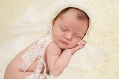 newborn baby girl wearing lace bonnet sleeping on her tummy, unique fine art baby portraits by Olga Klofac Professional Baby Photographer Charlestown Mayo