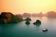 Ha Long Bay - Vietnam;  Listed in the UNESCO World Heritage Site, one of the new 7 wonders of the world, Ha Long Bay is composed of thousands of small islands and caves. DO kayaking in the bay!