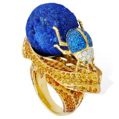 Lydia Courteille Sahara Featuring an industrious dung beetle rolling his precious cargo – a deep-blue ball of the copper mineral azurite – along the surface of the yellow gold ring. Set with azurite, haüynites, topazolites, hessonites, white diamonds and brown diamonds, orange and yellow sapphires. The blue and yellow Sahara desert sand and animal inspired jewellery collection by Lydia Courteille that is bright and exotic: http://www.thejewelleryeditor.com/jewellery/article/lydia...