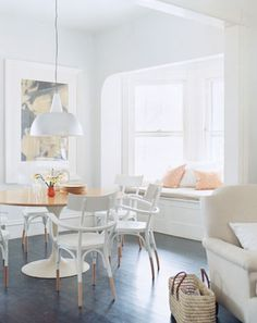 White furniture and walls, dark floors, light wood table, and orange accents make for a feminine, young dining area and reading nook!