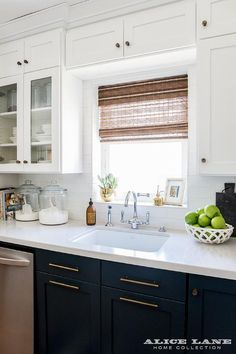 Navy blue kitchen cabinets are finished with long brass pulls and white quartz countertops holding a sink with a polished nickel gooseneck faucet under a window dressed in a bamboo roman shade and framed by white subway backsplash tiles and white shaker cabinets, including a glass front china cabinet located above glass storage jars.