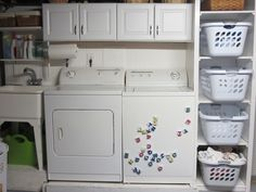 113 year old basement laundry area turned into a clean and functional space .    Laundry basket shelf and cabinets.