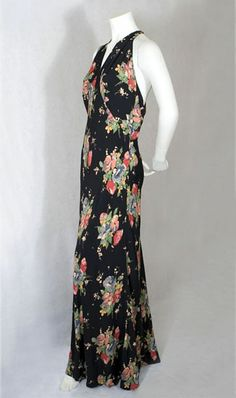 Bias cut floral silk crepe dress, c. 1930's. The dress is fashioned from navy/black silk crepe printed with large, cheerful floral bouquets. It has a softly draped and almost bare back with a halter neck.