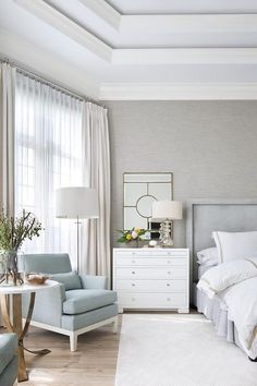 Under an octagon tray ceiling, this gorgeous gray bedroom is beautifully furnished with a gray velvet bed dressed in gold border hotel bedding paired with matching shams and positioned on a light gray rug beside a tall white nightstand lit by mercury glass lamp placed in front a mirror.