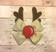 How cute is this Rudolph the Red Nose Reindeer inspired Bow!?! Beige bow is accented with a Red Nose and Antler felties to resemble Rudolph. Finished bow with felites is approx 4 wide and 5 tall. Bow is attached to a ribbon lined alligator clip, with your choice of either to be worn on