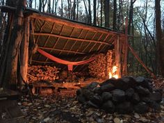 A lean-to with hammock and reflective fire. #survivalshelter