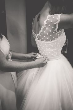 Bride getting ready in vintage polka dotted wedding dress with tulle skirt.