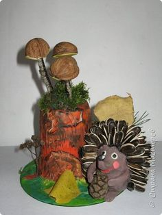 Осень, время поделок из природного материала...  Ёжик у пенька с грибами. В основе пенька пластиковый стаканчик от мороженого, и облеплен пластилином, мох; ёжик - киндер обмазан пластилином и украшен семенами подсолнечника; грибы (должны были быть опята, из палочек и шляпок от желудей, но в виду их отсутствия вышли другие грибочки) - березовые палочки, пластилин и скорлупа грецких орехов; в основании всей композиции диск компьютерный. фото 1
