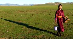 Jeune femme au petit matin, transportant ses outils de traite (Mongolie).