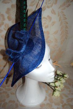 Tocado azul kklein con adorno sinamay y  pluma faisán