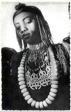 Africa | Toubou dancer adorned with jewels.  Zouar, Tibesti region in northern Chad | Postcard image, published by Bourdelon, ca. 1958//Le Borkou-Ennedi-Tibesti est une ancienne unité administrative du Tchad. Entre 2002 et 2008, le Borkou-Ennedi-Tibesti a été l'une des 18 régions du Tchad avec comme chef-lieu la ville de Faya-Largeau. Wikipédia