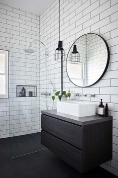 Bathroom White subway tiles are laid horizontally in this smaller bathroom, with the same large format black tiles on the floor. A circular mirror sits above a white basin and black timber vanity, with an industrial-style pendant lamp hangs above. Bathroom Renos, Bathroom Renovations, Bathroom Tray, Gold Bathroom, Round Mirror In Bathroom, Bathroom Lamps, Black Vanity Bathroom, Bathroom Accents, Bathroom Basin