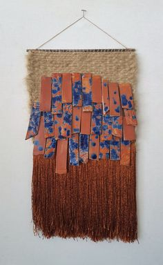 Hemp fiber weaving with shiny copper colored tassels. Hand made stoneware tiles hang from the weaving. Hangs from a steel rod. 12 wide x 21-22