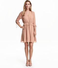 Knielanges Chiffonkleid mit V-Ausschnitt und bezogenen Knöpfen oben. Das Kleid hat eine elastische Taille mit  dekorativem Kordelzug und schmalem Volant. 3/4-lange Ärmel mit Gummizug und Bändchen unten. Teilgefüttert.