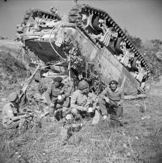 The crew of an upended Sherman tank of 7th Armoured Brigade enjoy a 'brew' beside their vehicle while waiting for a recovery team, Gothic Line, 13 September 1944. Their tank overturned after slipping off a narrow road in the dark.