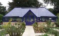 A bespoke freestanding greenhouse with a hipped roof in purple