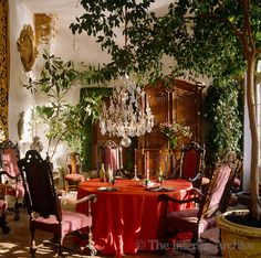 A summer room has been furnished for use as an alternative dining room with a crystal chandelier suspended low over the table