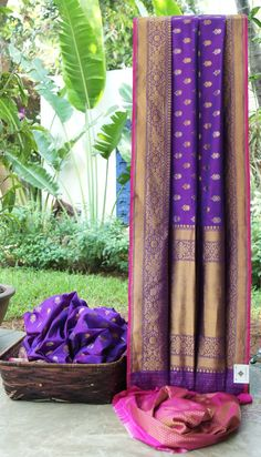 This Benares silk is in purple with gold and silver zari bhuttas all over. The border and pallu have an intricate weave of gold zari with a magenta selvedge. The blouse has a gold zari brocade in m…