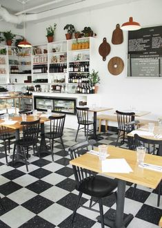 Luce restaurant in Portland, Oregon before opening. Checkerboard floors; white walls; open shelves of wine; charcuterie boards on walls.
