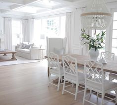 All white coastal styled interior with white walls, chairs, chandelier and sofa.