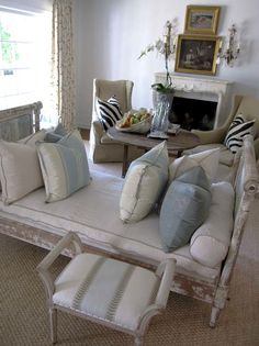 love the way the small picture is over the large picture..so tired of mirrors over mantels...great high back chairs and bench to utilize boths sides of a conversation area....