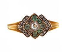 Cushion cut diamond ring surrounded with emeralds all in 18k gold. European in origin. Circa 1850-70.
