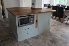 A kitchen island built around a pillar with a microwave on the left and a pull out bin on the right and oak pull out trays in the middle.