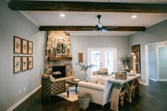 """FixerUpper2.3_039Joanna warmed up the living room by adding new stone to the fireplace, installing a bar top in the kitchen, and including large wooden beams. She added warm colors and dark floors to create contrast instead of the previous vanilla walls. The walls in the living spaces were all painted """"Magnetic Gray""""."""