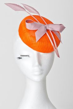 Orange sinamay base button comb fastening fascinator with dusky pink grosgrain bow and arrow feather accents