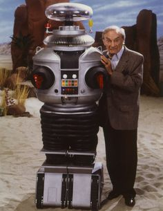 Publicity photo of Jonathan Harris also known as Doctor Smith of Lost in Space with the Robot - from Lost in Space Forever