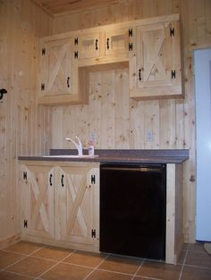 <p>This tack room features custom pine cabinets, a tile floor, sink