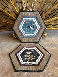 Beautiful pair of two hand embroidered silk/cloth trivets. Hexagon shape with silk center embroidery of birds. One black one teal. Some signs of use to black but teal in good vintage condition. Frame, or use in kitchen for protecting countertops from heat damage. I have large round embroidered panda trivets sold separately in shop. SOLD AS PAIR Measures each 7 x 8 hexagon Thanks for shopping YellowHouseDecor!  Please visit my sisters shop for more vintage items ( ellansrelics02)